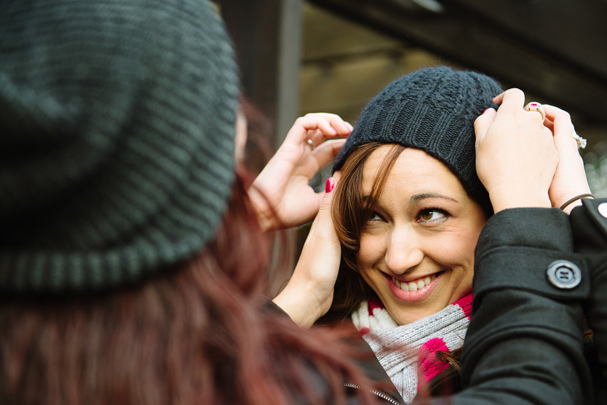 putting on winter hat for engagement session