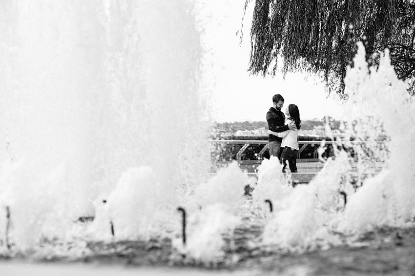 couple hugging in front of kennedy center water fountain