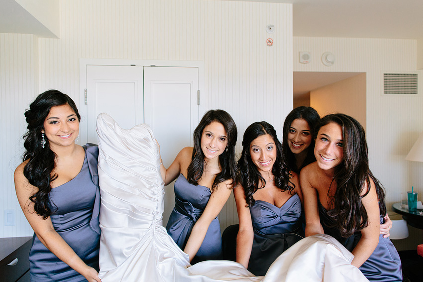 bridesmaids holding up wedding dress